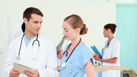 Two doctors looking at tablet computer with their colleagues behind Footage