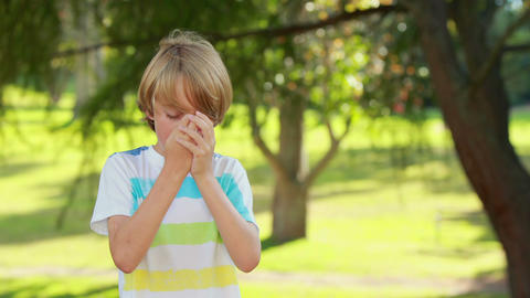 Little boy using his inhaler in the park Footage