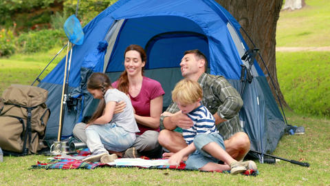 Happy family on a camping trip in front of their tent Footage