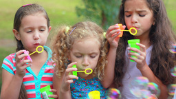 Children playing with bubble wand in the park Footage