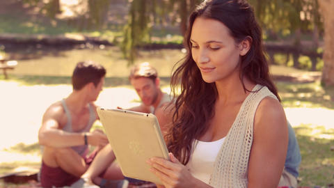 Woman using tablet computer with her friends behind her in park Footage