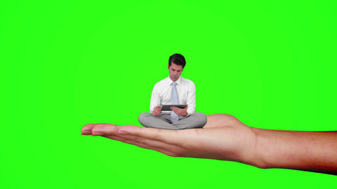 Hand holding sitting businessman focused on tablet computer against green screen Animation