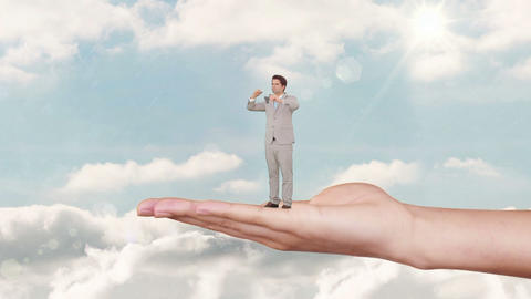 Hand holding standing businessman with binoculars against blue sky Animation