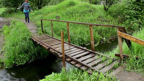 Woman Go Across A L Ittle River On A Wood Bridge Footage