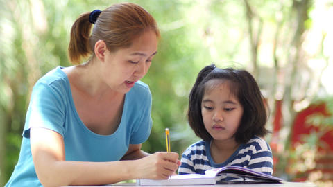 Little Asian girl with mother doing homework on the table, Pan shot Footage