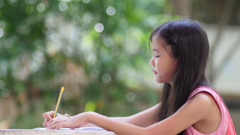 Little Asian Girl Doing Homework In The Garden At Home stock footage