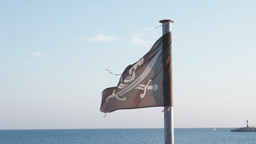 Black Pirate Flag Fluttering In The Sea Breeze stock footage