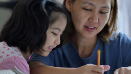 Little Asian girl with mother doing homework Footage