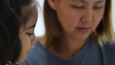 Close Up Of Little Asian Girl With Mother Doing Homework stock footage