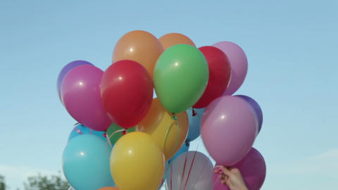Hand holding multicolored balloons Footage