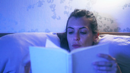 Frontal shot of a woman in bed reading a book Footage