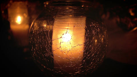 Candle inside cracked glass flickering in the dark Archivo
