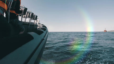 Side view of speedboat racing along the coast with a natural rainbow flare on th Acción en vivo