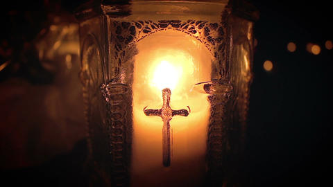 Single candle in thick glass container baring cross Archivo