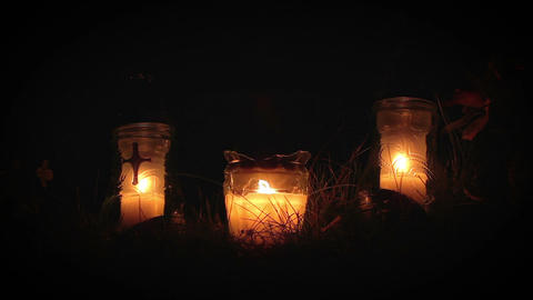 Three candles burning at night next to grave Archivo