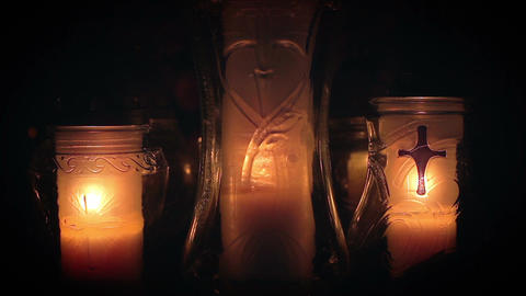 Three religious candles burning together in grave yard Footage