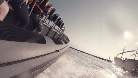 fast boat speeding around a larger ship into the sun Footage