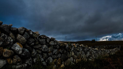 Wall made of rocks on a rural scene with wind turbines Stock Video Footage