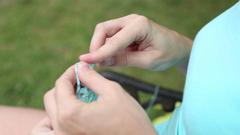 Woman knits via needle sweater yarn Footage