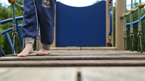 A boy walks barefoot on the playground Live Action
