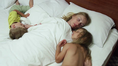 Woman lies in bed with her sleeping children Footage