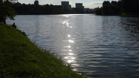 The lake with the fisherman and sun path (reflection) of Russia in the summer Footage