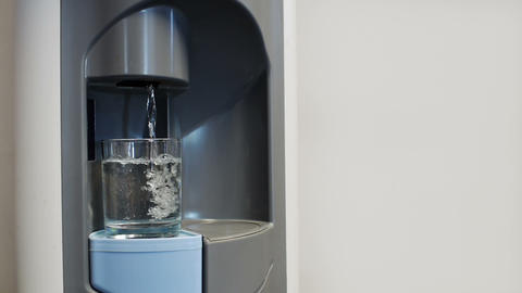 Filling small glass in water dispenser Footage