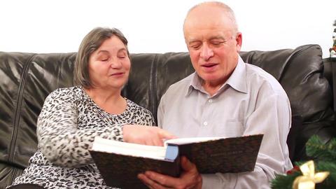 Senior couple going through photo album on Christmas 3 Live Action