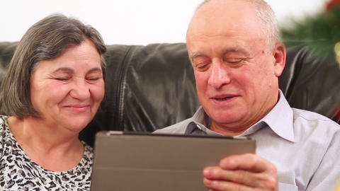 Senior couple using digital tablet at Christmas Footage