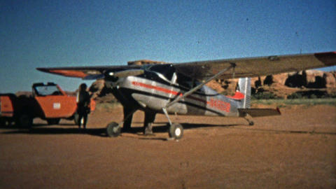 1971: Man cleaning the windshield of a small propeller touring airplane Footage