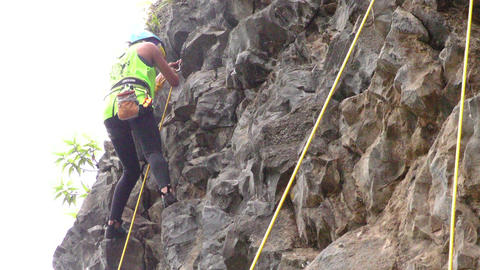 Young woman trying for the first time to rock climb low angle Footage