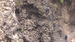 Group of unidentified people crossing over Tibetan bridge in Banos de Agua Santa Footage