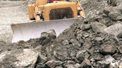 Front view of bulldozer moving rocks toward camera Footage