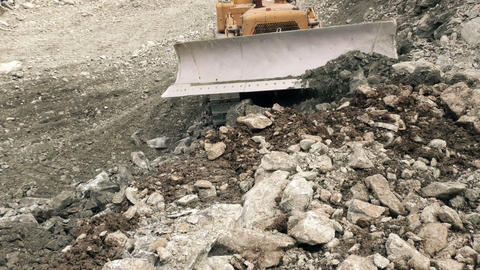 Front view of bulldozer moving rocks toward camera Footage