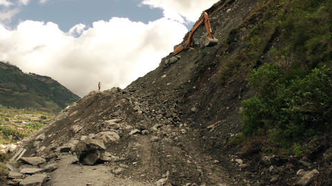 Large tracked backhoe cleaning landslide affected road Footage