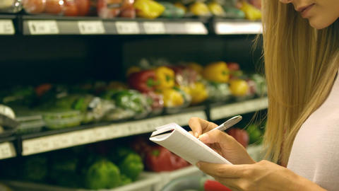 Woman checking her list while grocery shopping Footage