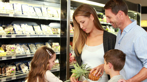 Family picking up pineapple in supermarket Footage