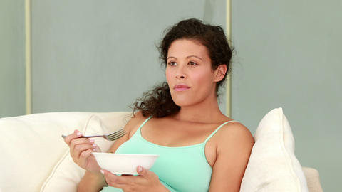 Pregnant woman eating salad on the couch Footage