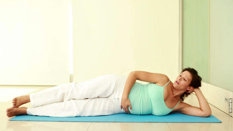 Pregnant woman exercising on exercise mat Live Action