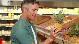 Smiling man choosing pineapple Footage