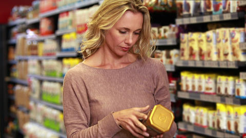 Pretty blonde putting product in trolley Footage