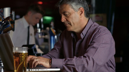 Frustrated Man Having A Pint At The Bar Using Laptop stock footage
