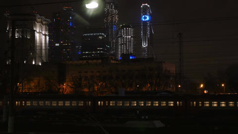Passenger train passing through the city at night Footage