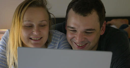 Couple watching humorous video on laptop Footage