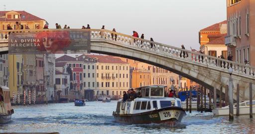 People crossing the bridge, water trams sailing beneath Footage
