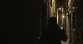 Woman running in dark alleyway at night Footage