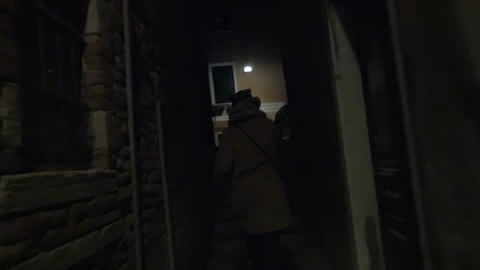 Woman running in narrow street at night Footage
