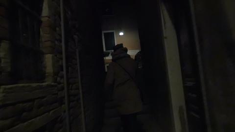 Woman running in narrow street at night Footage