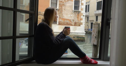Woman with tea enjoying scene from the window Live Action