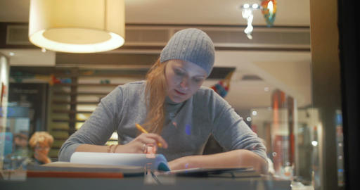 Woman in cafe working with pad and taking notes Footage